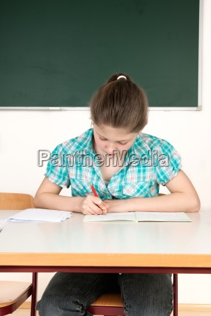 schoolgirl sitting at the table in