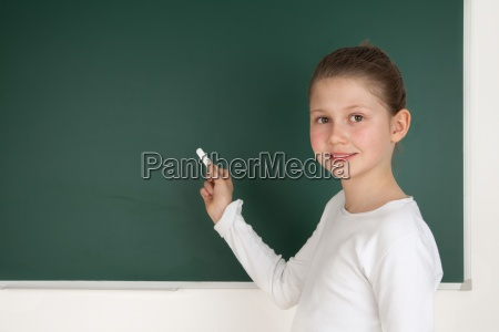 student standing in front of blackboard