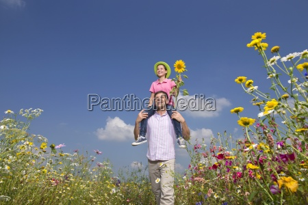 smiling father carrying daughter on shoulders