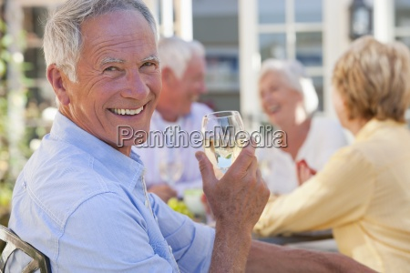 portrait of smiling senior man drinking