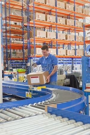 worker scanning cardboard box on production