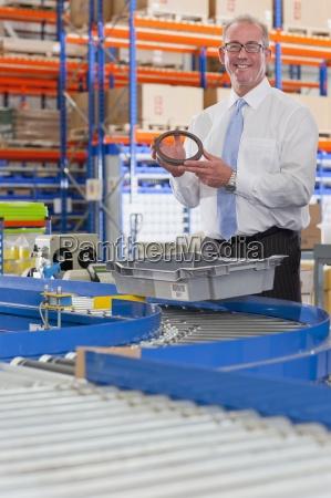portrait of smiling supervisor examining machine