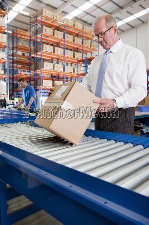 supervisor examining cardboard box on production