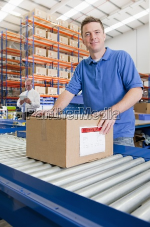 portrait of worker with cardboard box