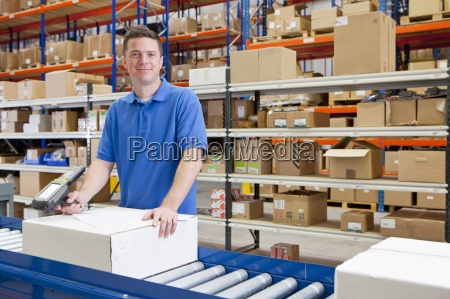 portrait of smiling worker scanning boxes