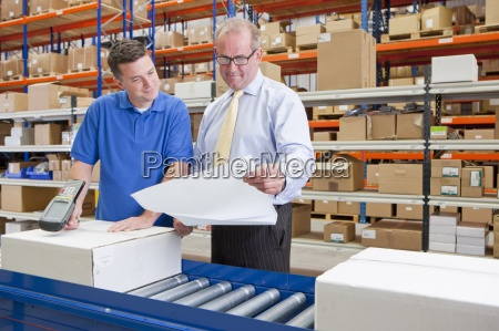 supervisor and worker examining paperwork and