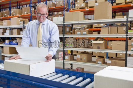 supervisor examining paperwork and boxes on