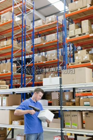 worker scanning box among shelves