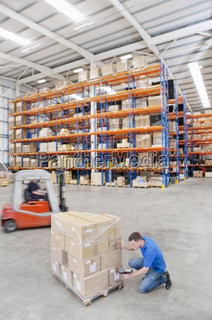 worker scanning cardboard boxes on pallet