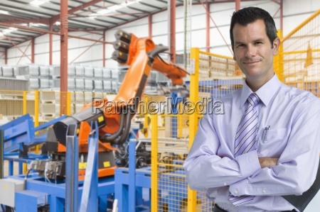 portrait of smiling businessman near robotic