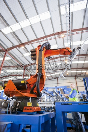 worker controlling robotic machinery lifting steel