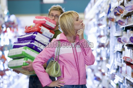 couple shopping in supermarket man struggling