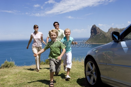 family running towards parked car on