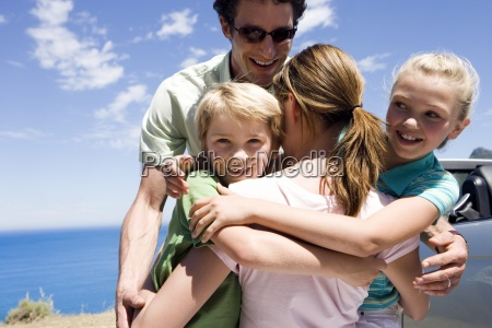 family embracing beside parked car on