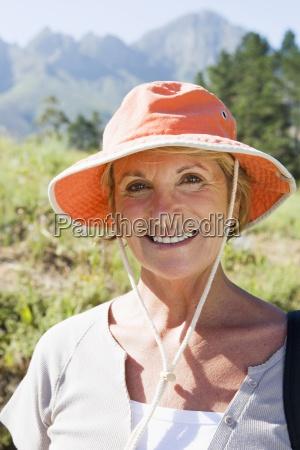 senior woman wearing orange sun hat