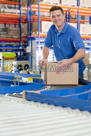 portrait, of, smiling, worker, with, cardboard - 12958644