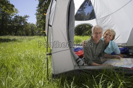 senior couple sitting inside tent in