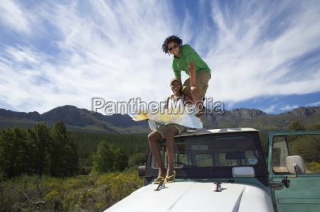 young couple sitting on roof of