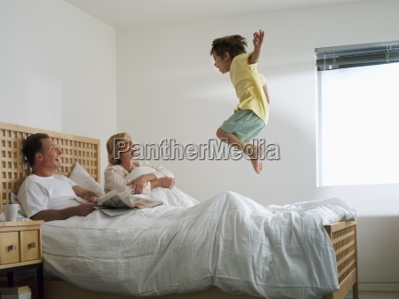 parents lying in double bed at