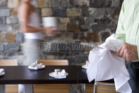 waiter and waitress laying tables in