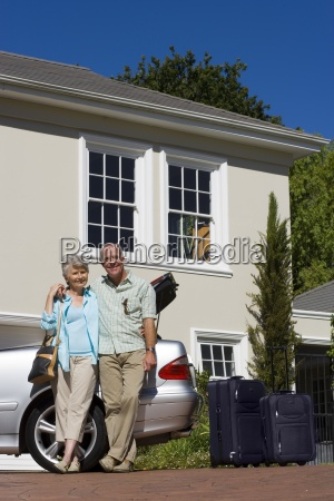 senior couple standing beside parked convertible