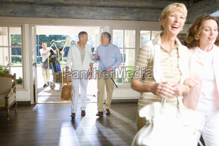 two mature couples entering hotel foyer