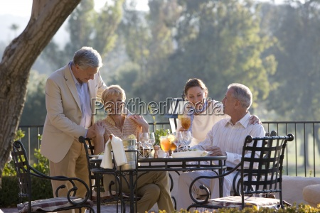 two mature couples dining at outdoor