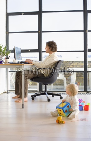 man using computer by window in