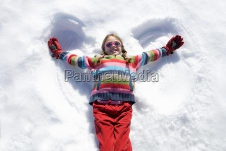 girl 7 9 lying in snow