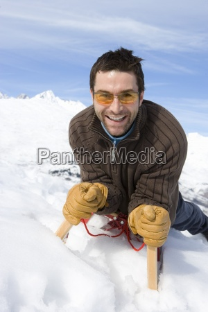 young man on sled in snow