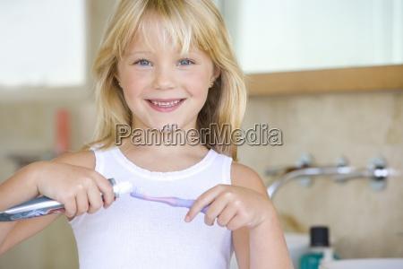 girl 6 8 applying toothpaste on
