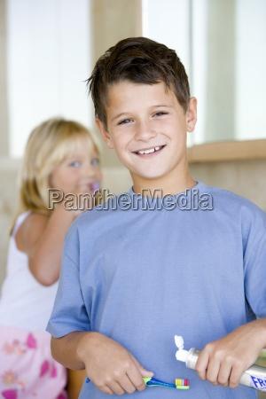boy 6 8 applying toothpaste on
