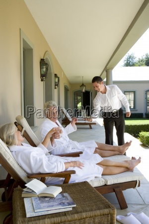 waiter standing by mature couple sitting
