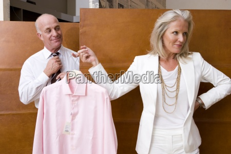 mature woman holding up shirt by