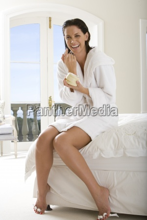 young woman sitting on bed painting