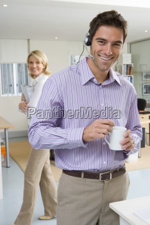 businessman wearing headset holding mug woman