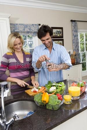 young man and woman making salad