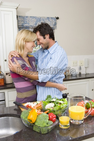 young couple embracing in kitchen by