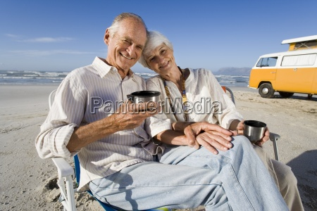 senior couple on beach by camper