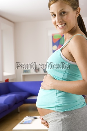 young pregnant woman with hands on