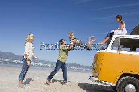 famiglia di quattro sulla spiaggia padre