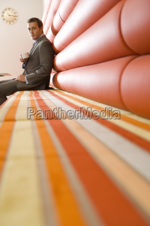 businessman with mug sitting beneath clock