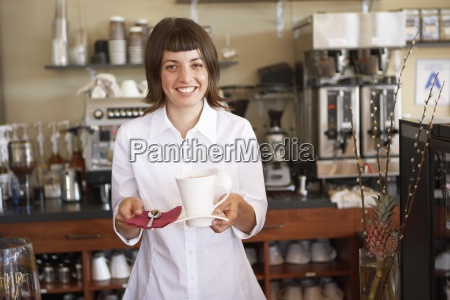 waitress serving behind counter in cafe