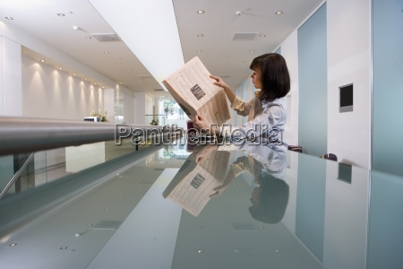 businesswoman reading financial newspaper in lobby