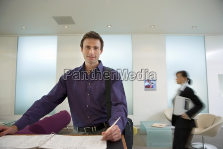 businessman signing guestbook in reception area