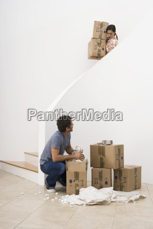 couple moving house woman carrying boxes
