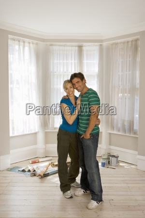 couple decorating at home standing in
