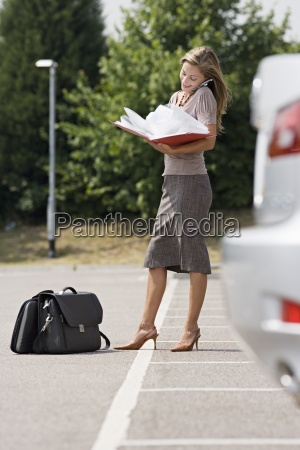 businesswoman standing in car park reading