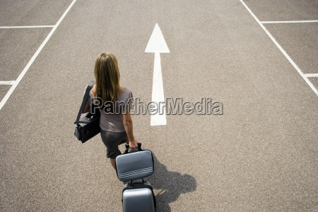 businesswoman walking with luggage in car