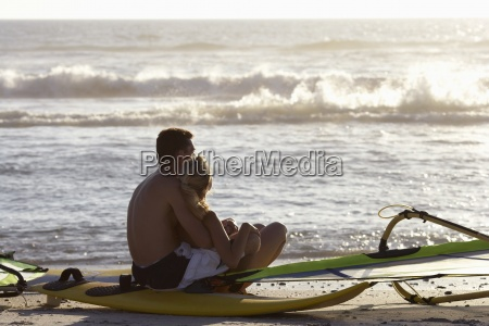 young couple sitting beside windsurfers on